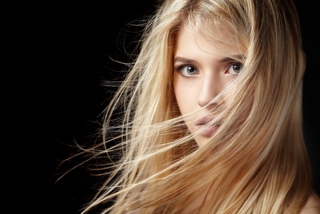 Close portrait of a beautiful young blonde woman with flying hair on a black background.