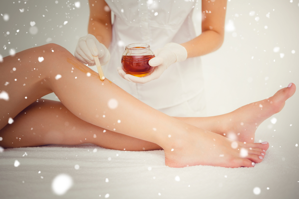 Snow against therapist waxing womans leg at spa center
