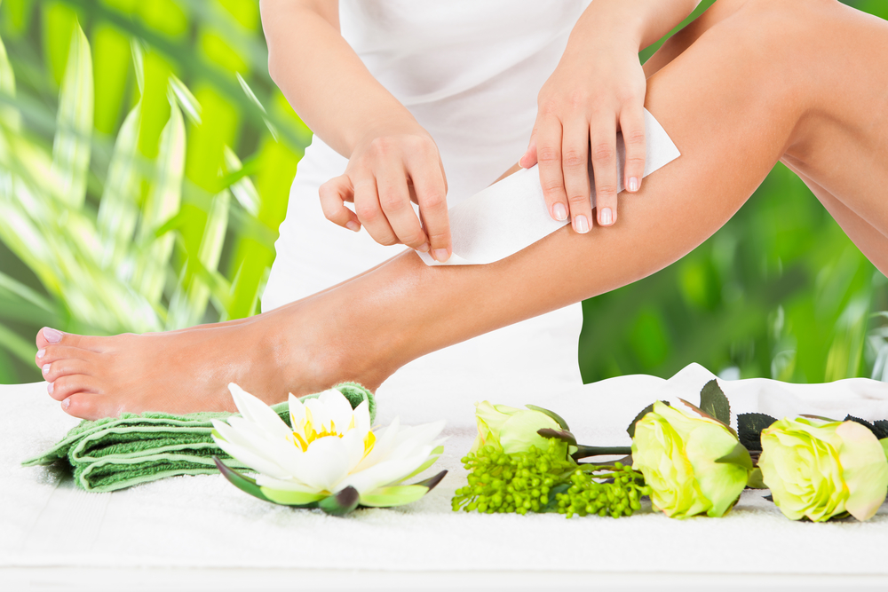 Beautician Waxing Woman's Leg In Spa