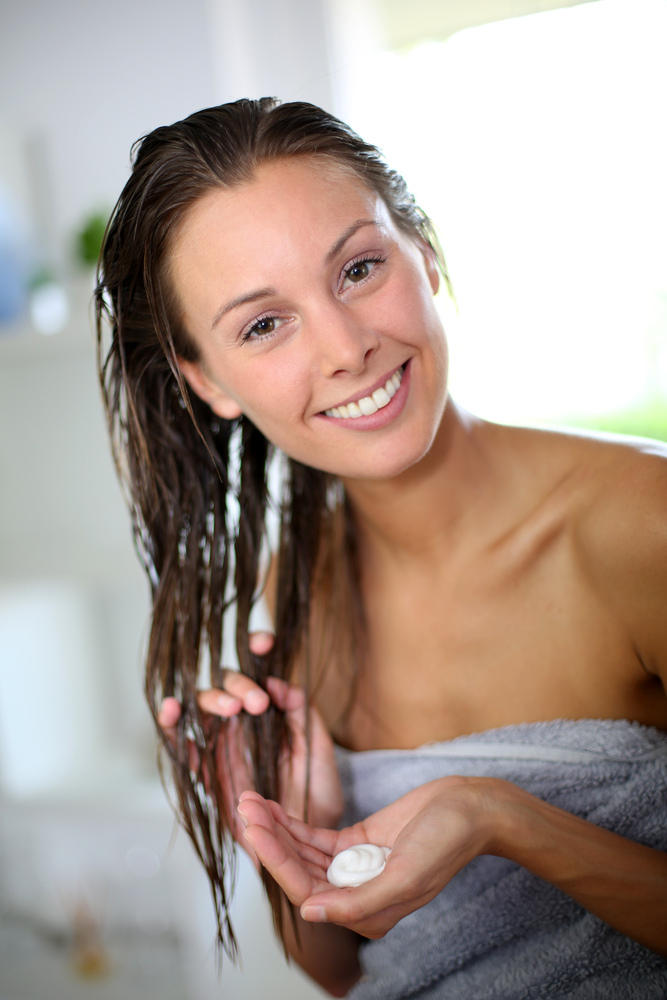 Gorgeous woman putting conditioner in her hair
