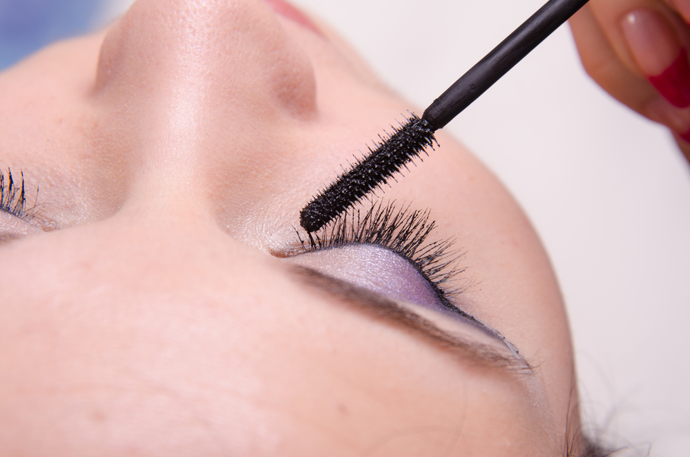 Makeup artist tints lashes mascara
