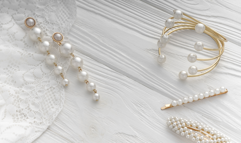 Top view of golden bracelet and earrings and hair pins with pearls jewelry on white wooden background