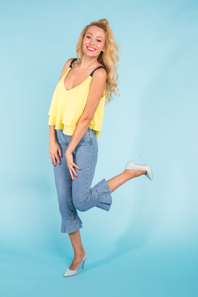 Portrait of funny emotional young blonde woman on blue background
